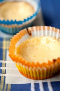 A condensed milk lemon tart in an orange and yellow cupcake wrapper on a blue tea towel.