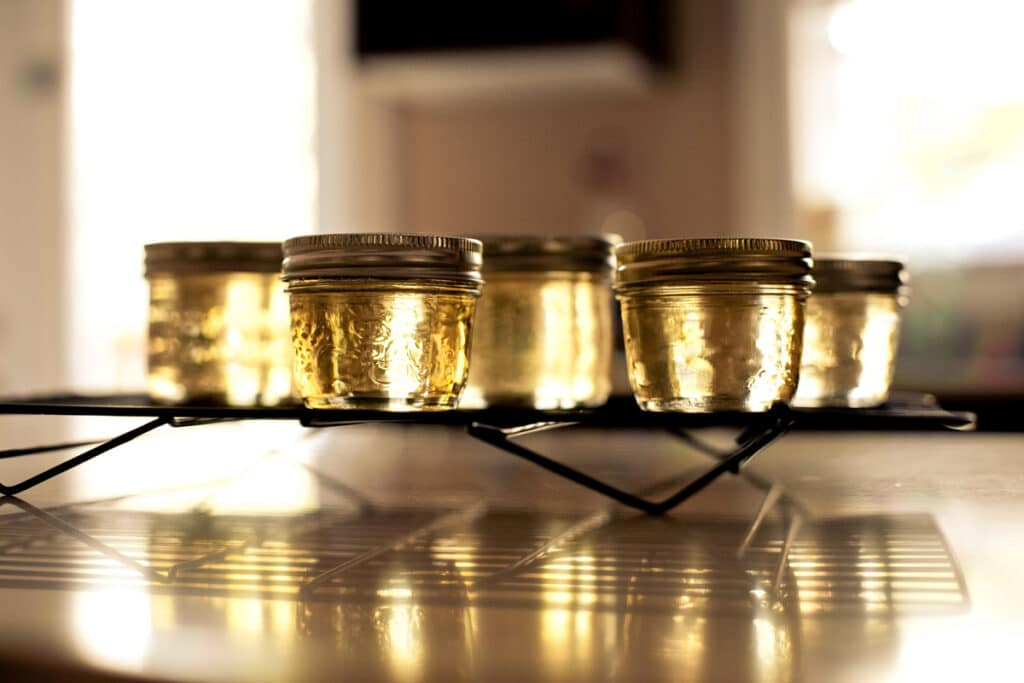 Small jars filled with TIdal Bay wine jelly cooling on a rack.