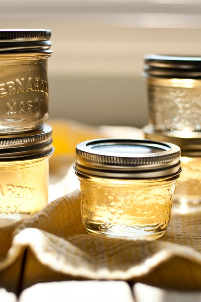 Jars of white wine jelly on a yellow cloth.