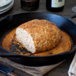 A butter chicken skillet meatloaf on a table with plates and wine.