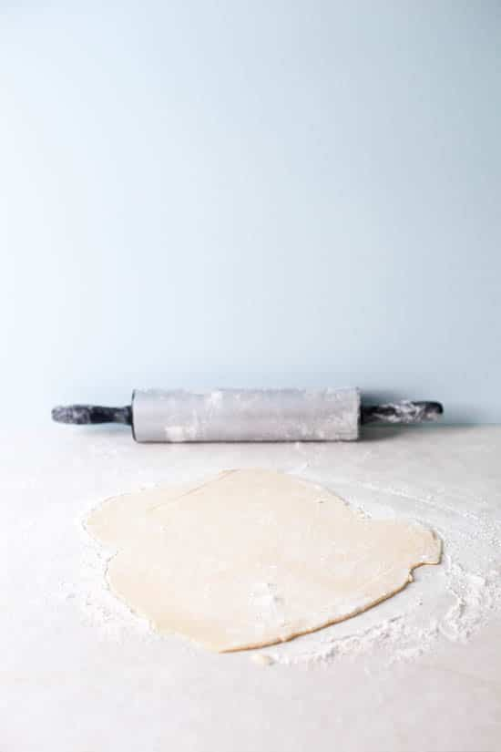 Rolled dough on a counter with a pin in the background.