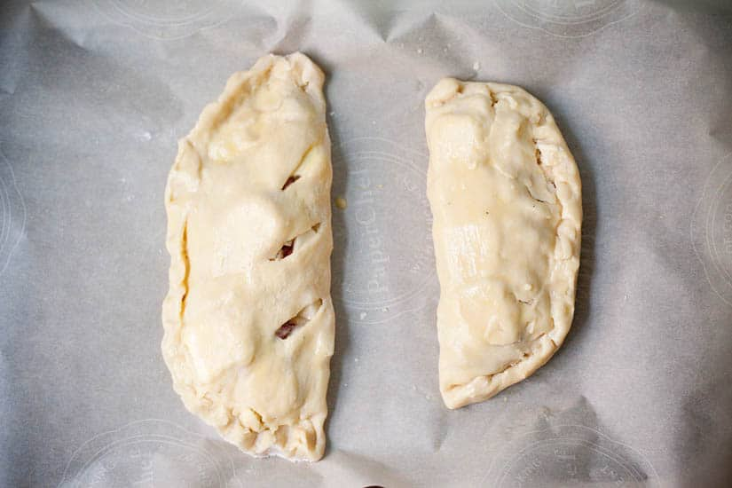 Pre-baked pastries on baking paper.