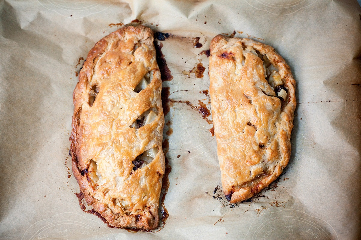 Two baked traditional Cornish pasties on a baking sheet.