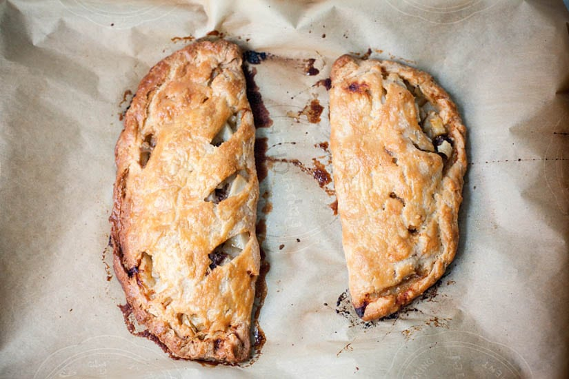 Two baked Cornish-style pasties on parchment paper.
