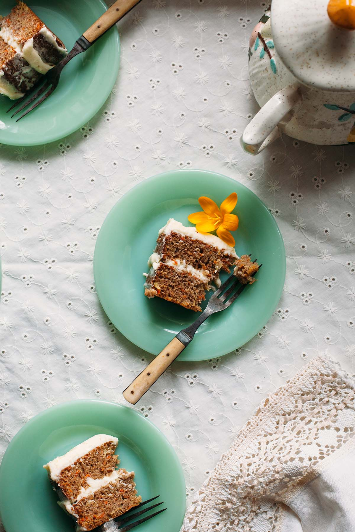 Overhead shot of a slice of spiced carrot cake on a green milk glass plate.