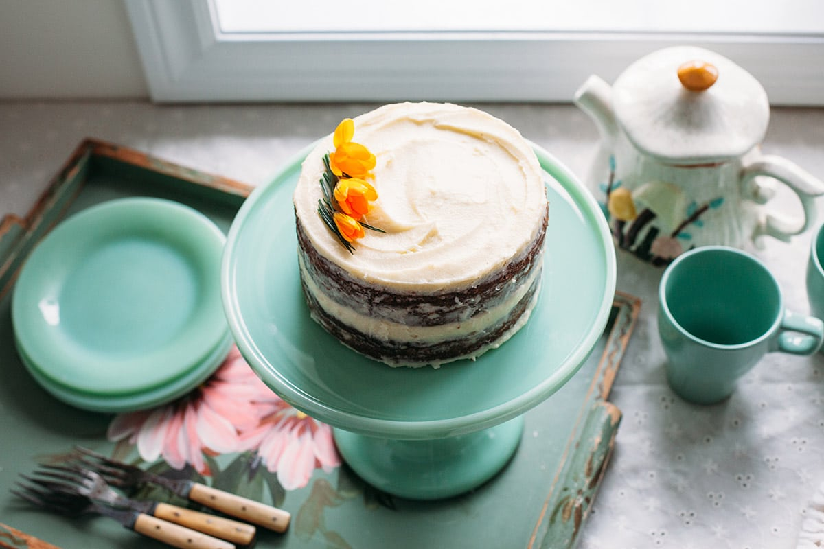 A cake decorated with yellow crocuses on a cake stand.
