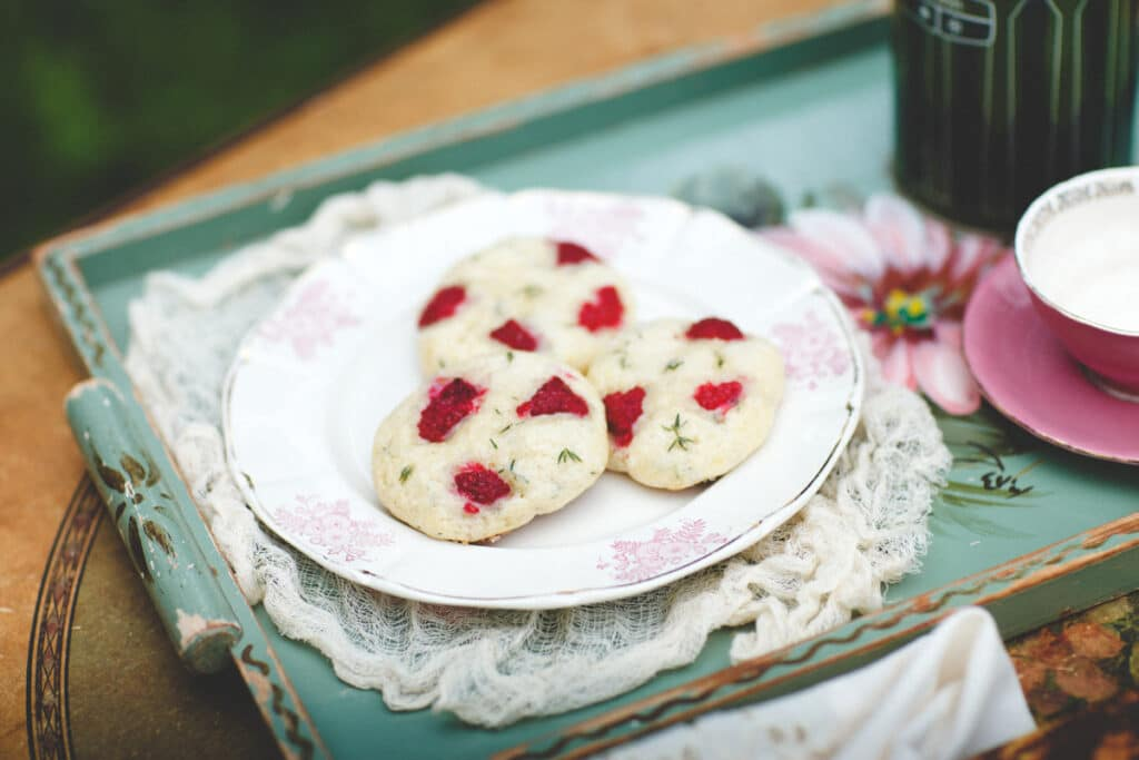 Three raspberry thyme scones on a plate on a green tray.