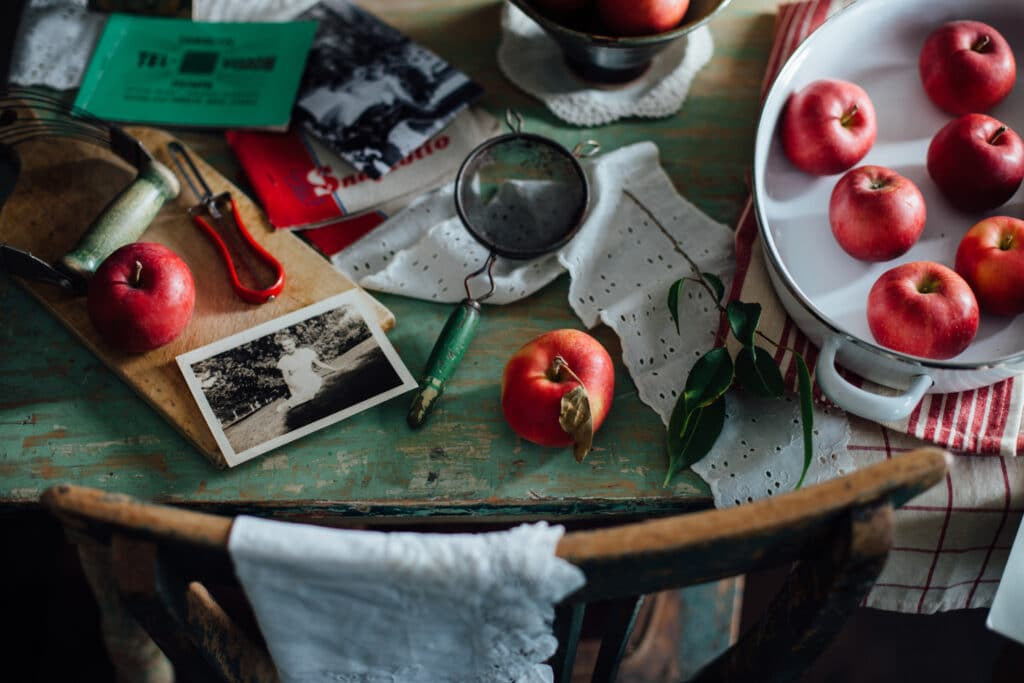 A green table with an assortment of apples, black and white photos, and fabric.