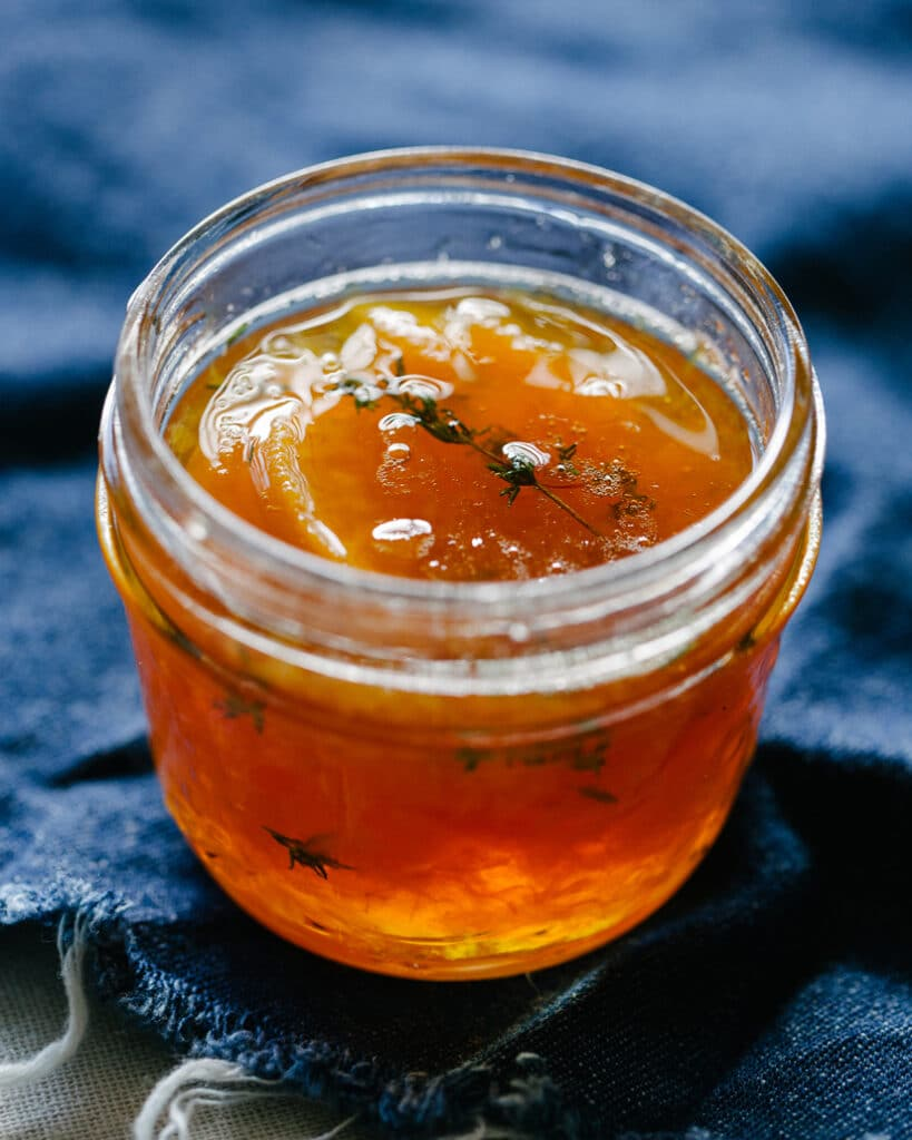 A small jar of jam backlit on a denim cloth.