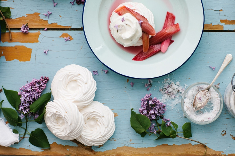 A table with meringue shells, lilac sugar, and one serving of rhubarb pavlova in a bowl.