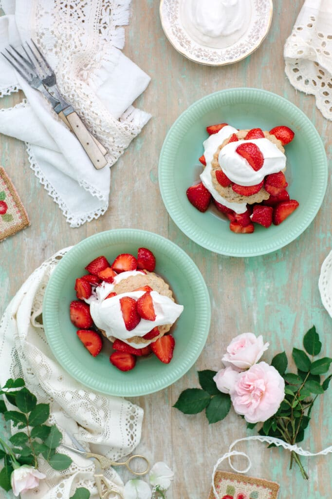 Overhead shot of strawberries, biscuits, and cream in bowls on a green table.