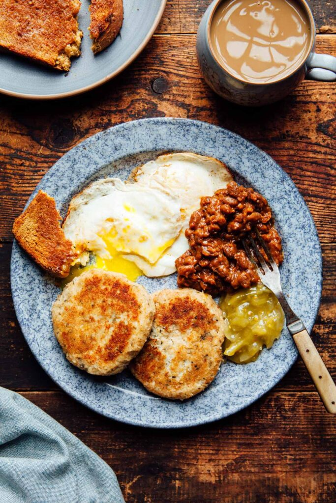 Fried eggs, fish cakes, and brown toast with a serving of homemade molasses baked beans with bacon.