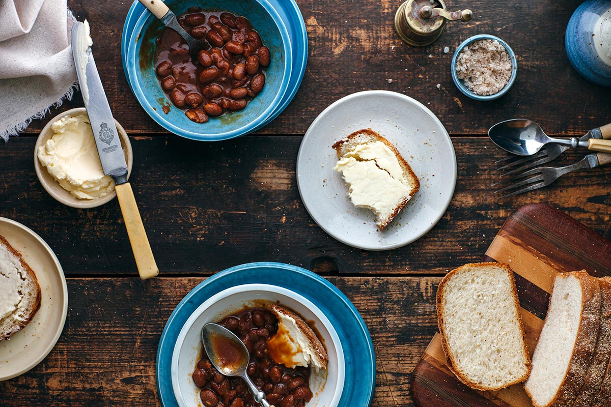 A table set with two servings of homemade molasses baked beans and bacon.