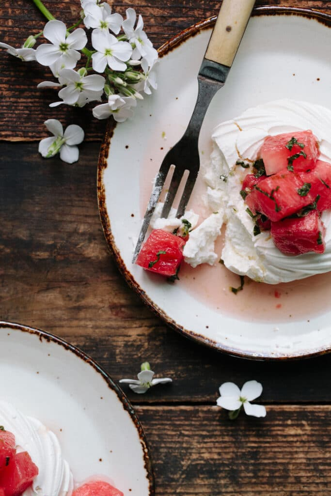 Single watermelon pavlova with one bite speared on a fork.