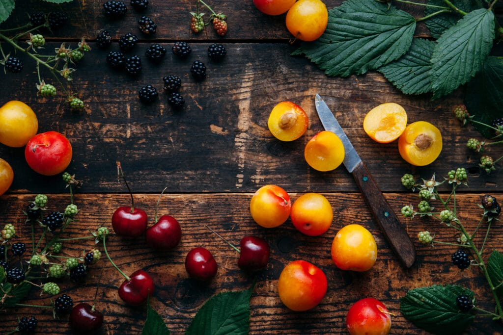 Yellow plums, cherries, and blackberries scattered on a farmhouse table.