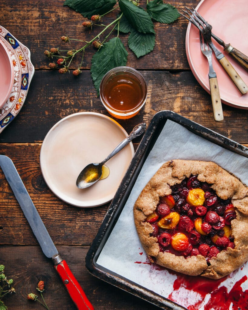 A whole berry and plum galette on a tray waiting to be cut with a long red-handled knife.