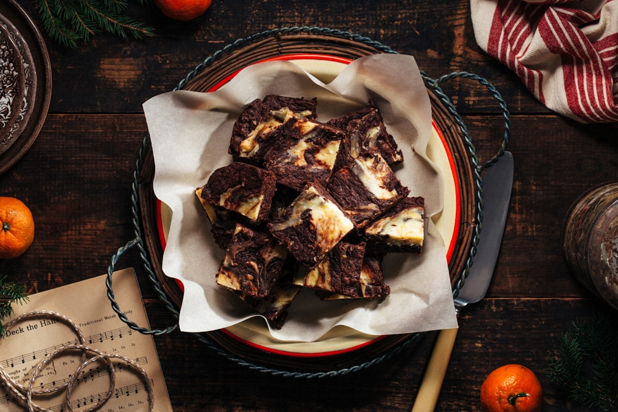 A round plate of dark chocolate brownies with cream cheese swirl surrounded by festive Christmas accoutrements.