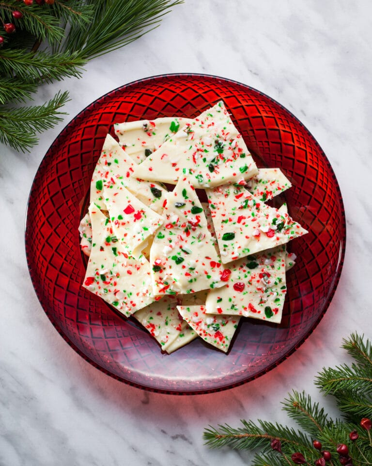 White chocolate candy cane bark on a red glass plate flanked by evergreen branches.