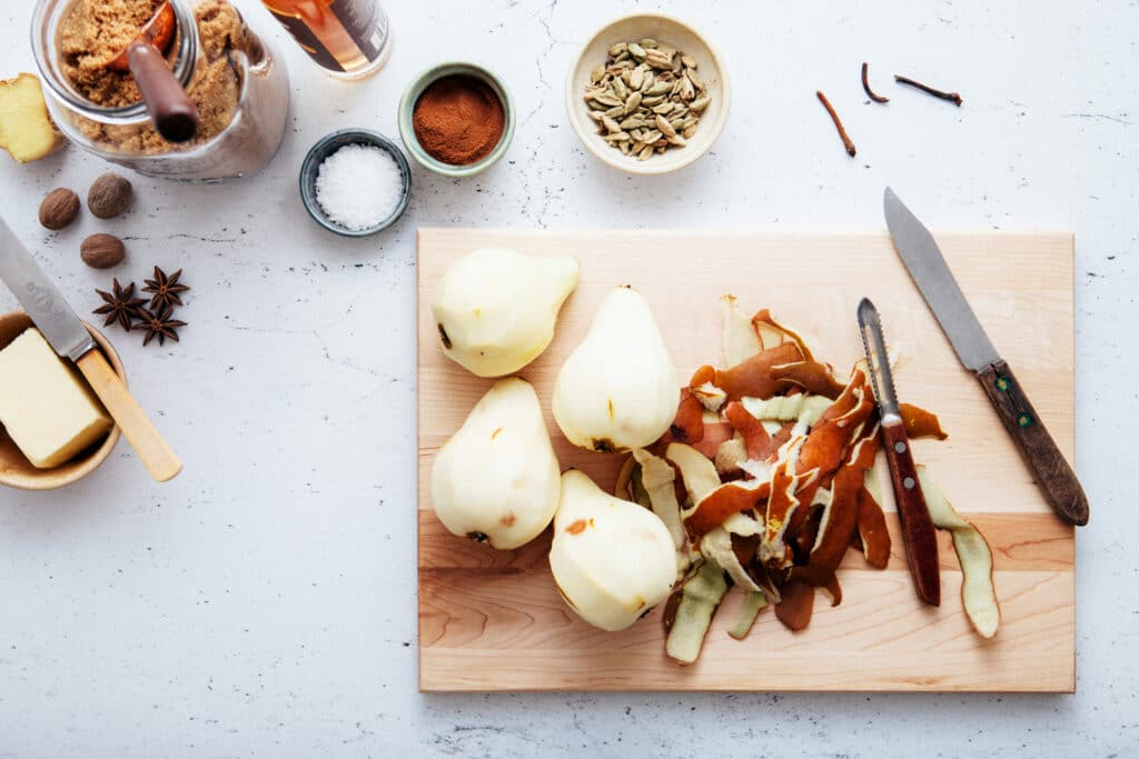 Peeled whole pears on a wooden cutting board waiting to be cut, cored, and roasted.