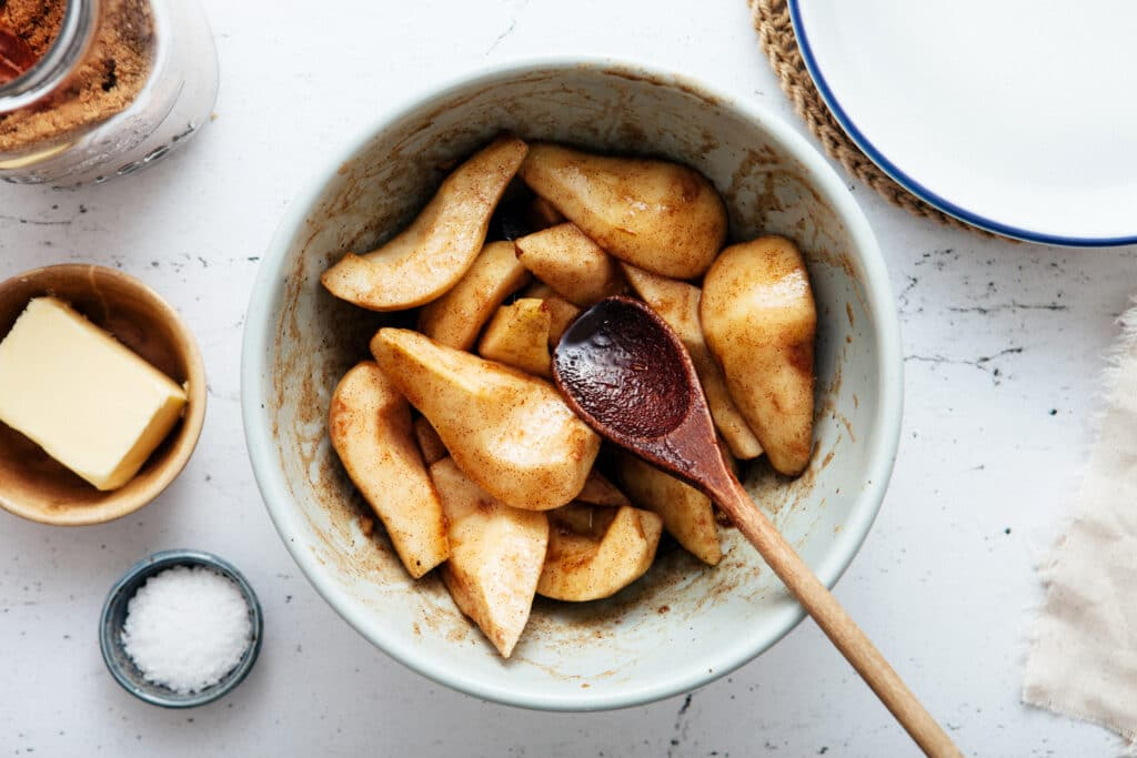 A bowl of pears tossed with spices in the process of being mixed with a wooden spoon.