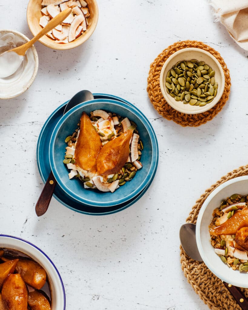 Oven roasted spiced pears on top of granola with yogurt in a bowl shot from overhead.