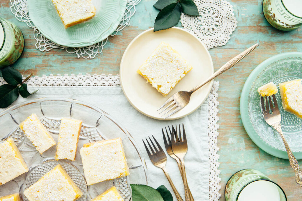 A classic lemon bar with shortbread crust on a small plate on a table.