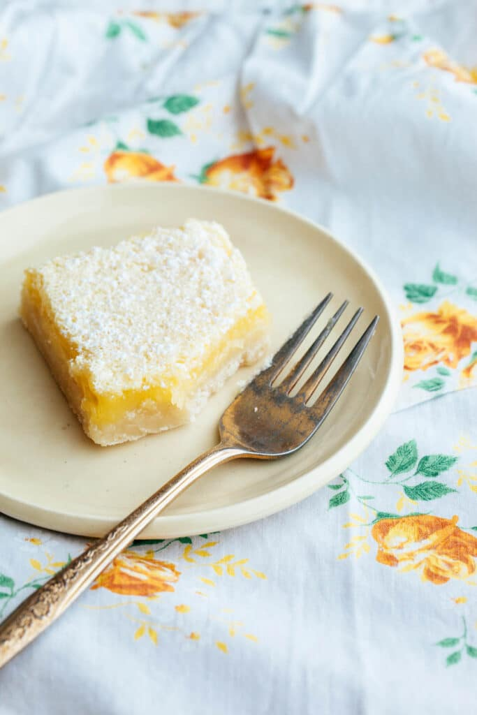 One lemon bar on a yellow plate with a gold fork.