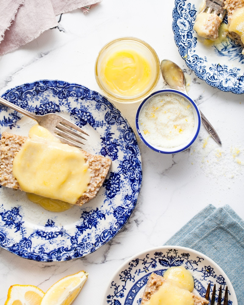 Microwave lemon curd spooned over slices of steel cut oats loaf on blue and white plates.
