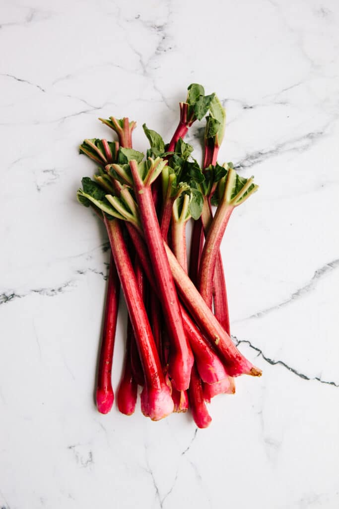 A bundle of rhubarb stalks on a marble background.