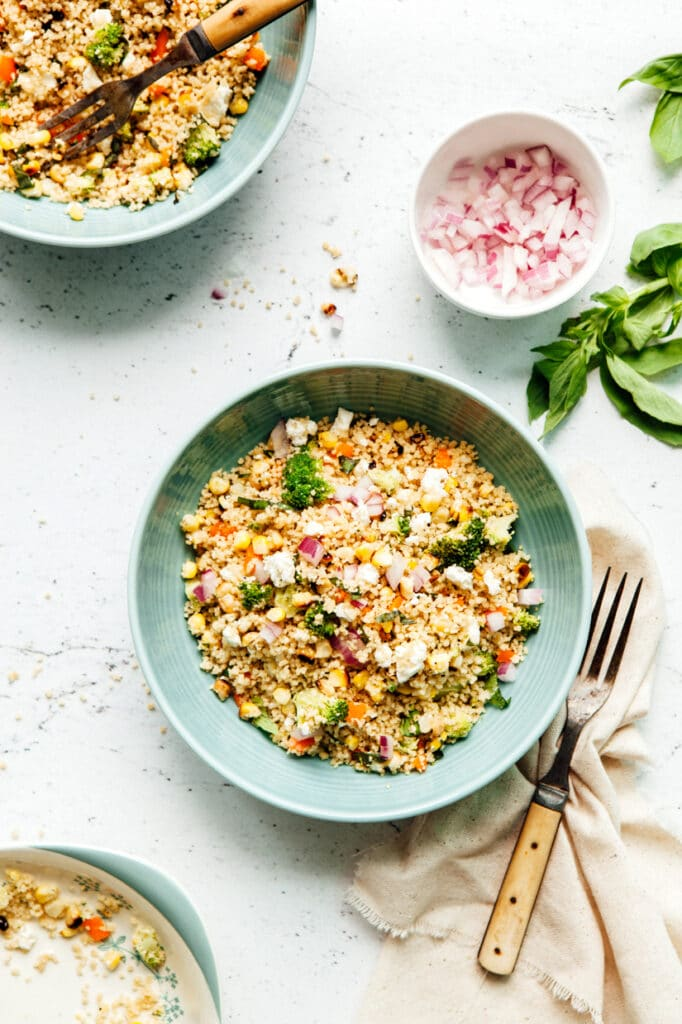 A bowl of charred corn couscous salad with feta and basil.