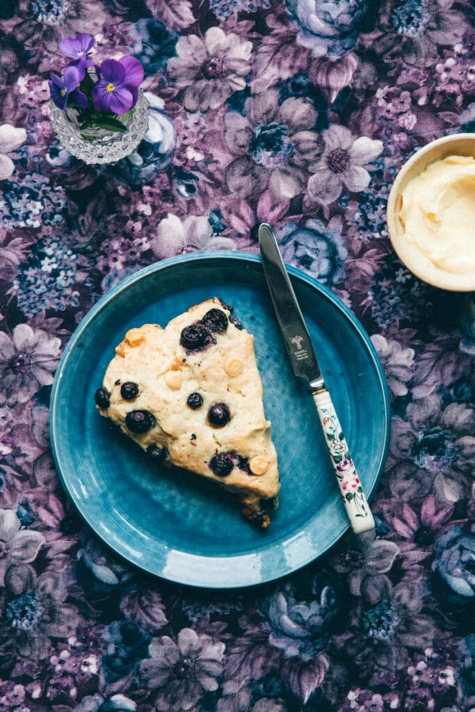 A scones on a blue plate with a small dish of butter and a small vase of purple pansies.