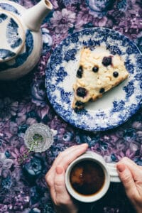 Hands holding a mug of tea next to a plate with a blueberry white chocolate scones