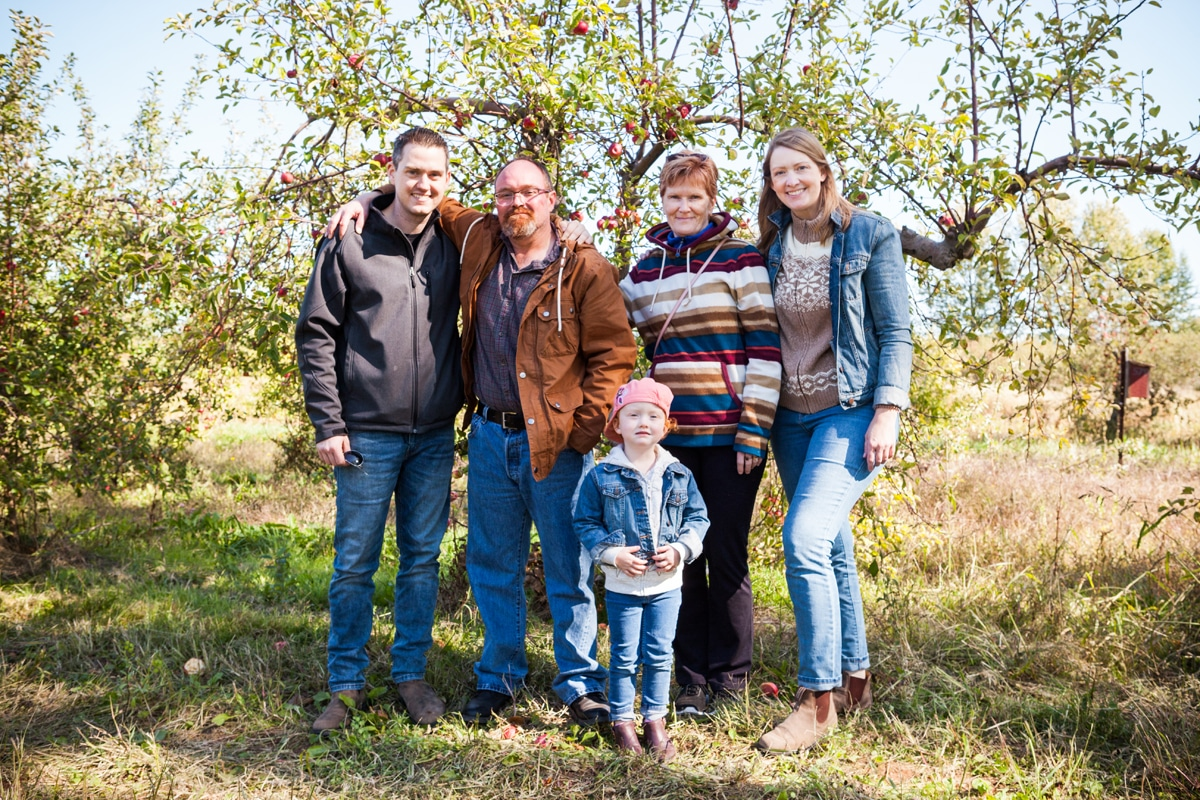 Kelly Neil and family in an apple orchard.