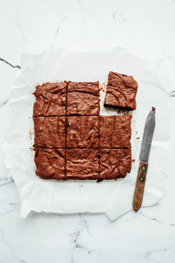 Nine double chocolate buckwheat brownies on a sheet of parchment paper alongside a knife