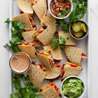 A pan of sheet pan cheeseburger quesadillas cut into wedges with bowls of condiments.