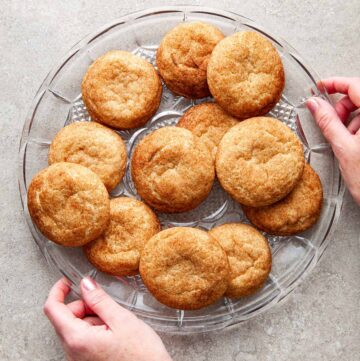 A large glass of platter of snickerdoodles without cream of tartar with two hands holding the edges of the platter.