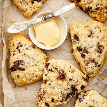Date and orange scones piled ina. box lined with parchment paper with a small dish of butter and a tiny pearl-handled knife.